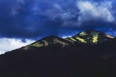 Dunkle Wolken hingen über der Spitze des Berges Stockfotografie