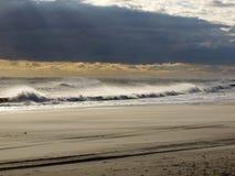 Dunkle Wolken treffen goldenes Meer Stockbilder