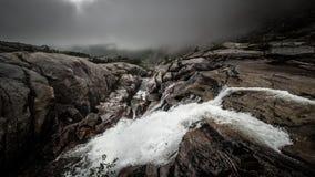 Dunkle Wolken und ein rauer Wasserfall Stockbilder