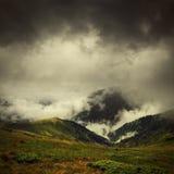 Dunkle Wolken und Nebel über Gebirgstal stockbilder