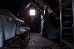 Dunkler Dachboden mit einem belichteten Fenster Lizenzfreie Stockfotos