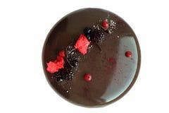 Dunkler glasig-glänzender Schokoladenkuchen mit Beeren auf weißem Hintergrund lizenzfreie stockfotografie
