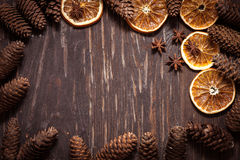 Dunkler hölzerner Hintergrund mit Kegeln, Sternanis, trockene Orange mit Co Lizenzfreie Stockbilder