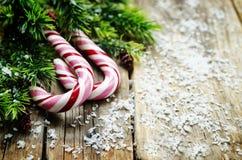 Dunkler hölzerner Hintergrund mit Weihnachtsbaum und Süßigkeit Stockfotografie