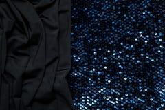 dunkler Hintergrund des schwarzen Gewebes und der glänzenden Stücke Stockbilder