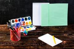 Dunkler Holztisch mit Bleistifthalter, bunte Bleistifte, Notizbuch Lizenzfreie Stockfotografie