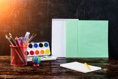 Dunkler Holztisch mit Bleistifthalter, bunte Bleistifte, Notizbuch Stockfotos