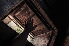 Dunkler Innenraum des Schmutzes mit der offenen verrosteten Tür- und Manneshand Stockfoto