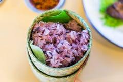 Dunkler klebriger Reis innerhalb des Bambusbehälters Gekochtes schwarzes klebriges Stockfoto