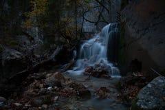 Dunkler magischer Kaskadenwasserfall im Herbst. Lizenzfreie Stockfotos