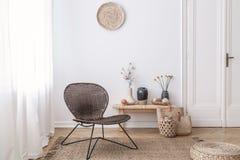 Dunkler, moderner geflochtener Stuhl in einem weißen Wohnzimmerinnenraum mit einer Holzbank und Dekorationen gemacht von den natü lizenzfreie stockbilder