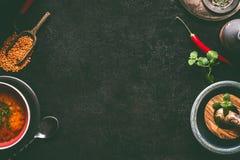 Dunkler Nahrungsmittelhintergrund mit heißen Linsensuppe- und kochenbestandteilen, Draufsicht, Rahmen Gesundes Veganessen stockbild
