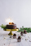 Dunkler Schokoladenkuchen mit Wunderkerzen und Beeren der kleinen Kuchen auf weißem hölzernem Hintergrund Stockfoto