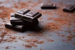 Dunkler Schokoladenstapel mit Kakaopulver auf einem Steinhintergrund mit Kopienraum Stockbilder