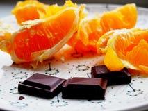 Dunkler Schokoriegel mit einer Orange Stockfotografie