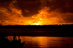 Dunkler Sonnenuntergang über dem Meer mit Boot Stockfotos