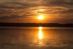 Dunkler Sonnenuntergang über dem See Stockfoto