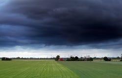 Dunkler stürmischer Himmel über Sommerackerland lizenzfreies stockbild