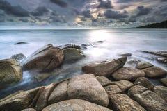 Dunkler Stein auf dem Strand Stockbilder