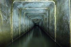 Dunkler und gruseliger überschwemmter Untertageabwasserkanalbetontunnel Flüssiger Wurf des industriellen Abwassers und des städti Lizenzfreie Stockfotos
