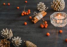 Dunkler Weihnachtshintergrund mit Kerzen und Beeren der Eberesche Kegel der weißen Kiefer Verzweigt sich Eicheln Stockfoto