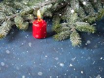 Dunkler Weihnachtshintergrund mit roter Kerze Stockfotografie