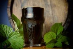 Dunkles Bier des halben Liters freundlich mit einem Blatt von Hopfen auf dem Hintergrund des Fasses Abschluss oben stockfotos