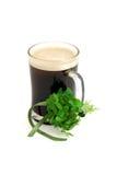 Dunkles Bier im Glas und im Blumenstrauß des falschen Shamrocks Lizenzfreie Stockfotografie