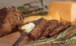Dunkles Brot mit Nüssen und Rosinen, Butter und Käse Stockbilder