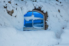 Dunkles Fenster in einer Kälte, Nacht des verschneiten Winters Stockfotografie