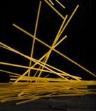 Dunkles Foto der rohen Spaghettilevitation auf schwarzer Hintergrundnahaufnahme Stockbild