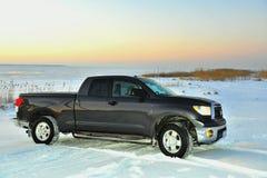 Dunkles Grau SUV auf dem Schnee deckte See ab. Stockbilder