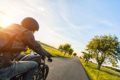 Dunkles Motorrad der motorbiker Reithohen leistung im Sonnenuntergang lizenzfreie stockfotos