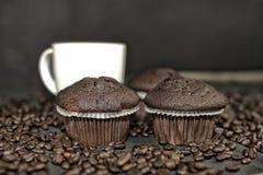 Dunkles Muffin, Tasse Kaffees und Kaffeebohnen auf schwarzem Hintergrund Addieren Sie dunkle Kontraste Lizenzfreies Stockbild