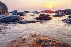 Dunkles Nachtmeer mit hervorstehenden Steinen Stockfotografie