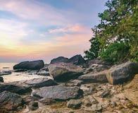 Dunkles Nachtmeer mit hervorstehenden Steinen Stockfotos