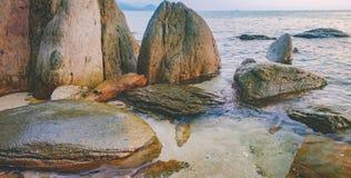 Dunkles Nachtmeer mit hervorstehenden Steinen Stockfoto