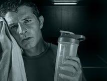 Dunkles nerv?ses Portr?t des jungen verschwitzten m?den und ersch?pften Sportmannes mit der Wasserflasche, die weg nach hartem Ei lizenzfreie stockfotografie