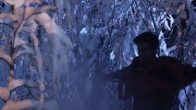 Dunkles Schattenbild des jungen Mannes bewegend in Wald des verschneiten Winters nachts stilles stock video