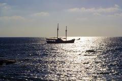 Dunkles Schattenbild des Schiffs im Meer bei Sonnenuntergang Lizenzfreie Stockfotos