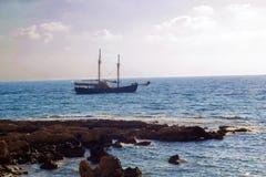 Dunkles Schattenbild des Schiffs im Meer bei Sonnenuntergang, weißer greller Glanz der Einstellung Lizenzfreies Stockfoto