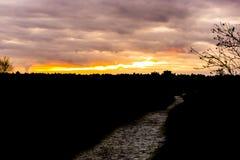 Dunkles Schattenbild einer Heidelandschaft mit einer gehenden Straße am Sonnenuntergang, am bunten Effekt im Himmel und an den Wo lizenzfreies stockfoto