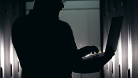 Dunkles Schattenbild eines Mannes, der auf einem Laptop schreibt stock video footage