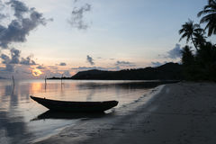 Dunkles Seetropischer Sonnenuntergang auf dem Hintergrundboot Stockfotos