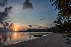 Dunkles Seetropischer Sonnenuntergang auf dem Hintergrundboot Stockbild