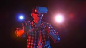 Dunkles Studio mit Flutlichtern Mann Gamer in den Gläsern der virtuellen Realität stock video footage