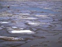 Dunkles Wasser, das durch shattern Eis kommt Stockfotos