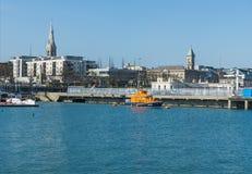 DunLaoghaire hamn och R n L I livräddningsbåt på kusten av ståndsmässiga Wicklow i Irland på en lugna vårmorgon Royaltyfria Bilder