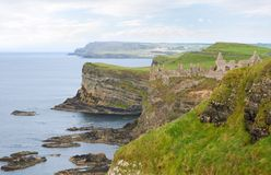 Dunluce Castle. Ruins of Dunluce Castle, Co. Antrim, N Ireland, with the cliffs of the Giant's Causeway in the background. The castle kitchens famously fell into royalty free stock photos