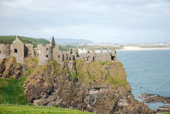 Dunluce Castle & Portrush. The cliffside ruins of Dunluce Castle with the beaches and town of Portrush in the background Stock Photos